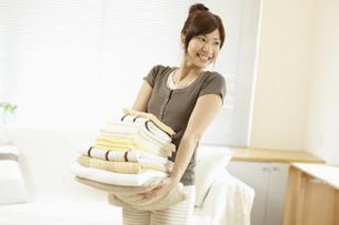 タオルを運ぶ女性の写真素材 [FYI03049549]