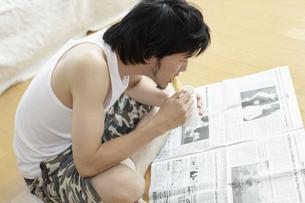 新聞を読みながらインスタント食品を食べる男性の写真素材 [FYI03049554]