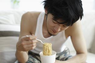 インスタント食品を食べる男性の写真素材 [FYI03049557]