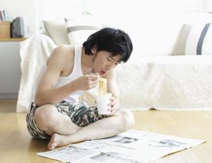 新聞を読みながらインスタント食品を食べる男性の写真素材 [FYI03049560]