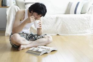 漫画を読みながらインスタント食品を食べる男性の写真素材 [FYI03049565]