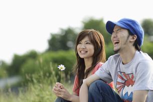 草原に座るカップルの写真素材 [FYI03049623]