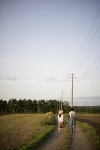 田舎道を歩くカップルの写真素材 [FYI03049807]