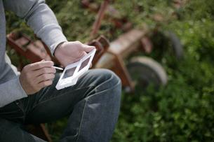 携帯型ゲーム機で遊ぶ男性の写真素材 [FYI03049871]