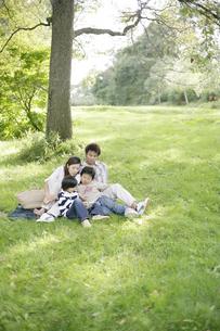 芝生の上でくつろぐ親子の写真素材 [FYI03049892]