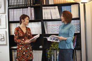 本棚の前で会話するビジネスウーマンの写真素材 [FYI03049941]