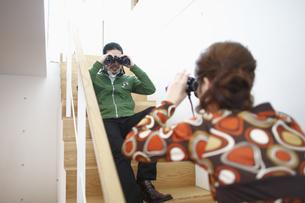 階段で双眼鏡をのぞき合う男女の写真素材 [FYI03049958]