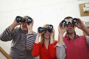 双眼鏡を覗く男女の写真素材 [FYI03049969]