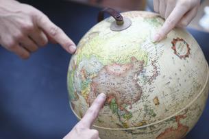 地球儀を指差す手の写真素材 [FYI03050019]