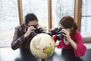 地球儀を双眼鏡でのぞく男女の写真素材 [FYI03050022]