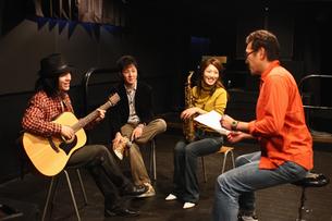 レコーディングスタジオで話し合う若者たちの写真素材 [FYI03050128]