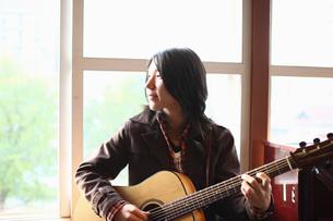 窓際に立つギタリストの写真素材 [FYI03050140]