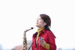 音楽を聴くサキソフォンを持った女性の写真素材 [FYI03050155]