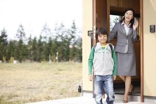 玄関を出る息子と見送る母親の写真素材 [FYI03050533]