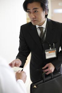 名刺を渡すビジネスマンの写真素材 [FYI03050621]