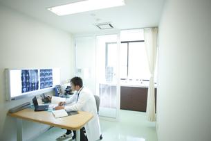 診察室で仕事をする医師の写真素材 [FYI03050692]