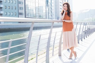 街中の川沿いに立つ女性の写真素材 [FYI03053813]
