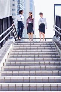 ビル街の階段を降りるビジネスウーマンの写真素材 [FYI03053828]