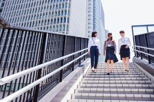 ビル街の階段を降りるビジネスウーマンの写真素材 [FYI03053836]