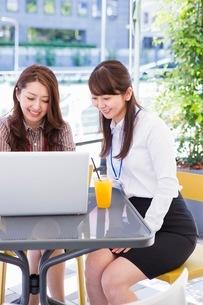 オープンカフェでパソコンを開くビジネスウーマンの写真素材 [FYI03053968]