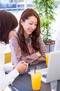 オープンカフェでパソコンを開くビジネスウーマンの写真素材 [FYI03053970]
