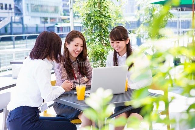 オープンカフェでパソコンを開くビジネスウーマンの写真素材 [FYI03053972]