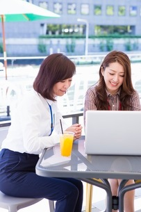オープンカフェでパソコンを開くビジネスウーマンの写真素材 [FYI03053973]