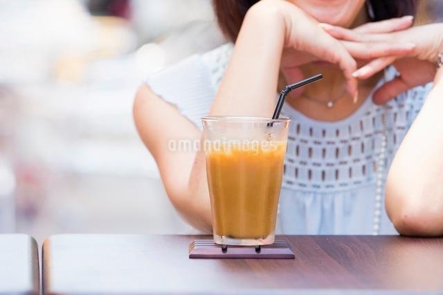 オープンカフェで過ごす女性とアイスコーヒーの写真素材 [FYI03054007]