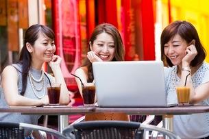 オープンカフェでパソコンを開く女性の写真素材 [FYI03054010]