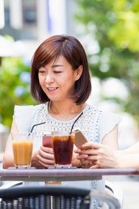 オープンカフェでスマホを操作する女性の写真素材 [FYI03054013]