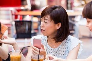 オープンカフェでスマホを操作する女性の写真素材 [FYI03054016]