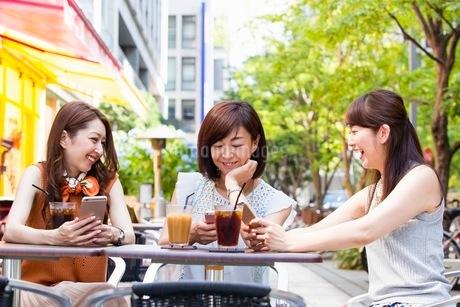 オープンカフェでスマホを操作する女性の写真素材 [FYI03054020]