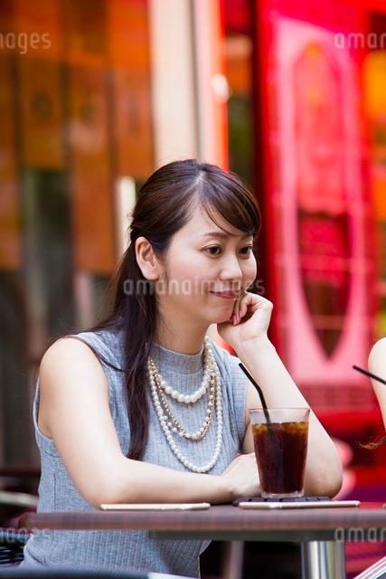 オープンカフェで頬杖をつく女性の写真素材 [FYI03054022]