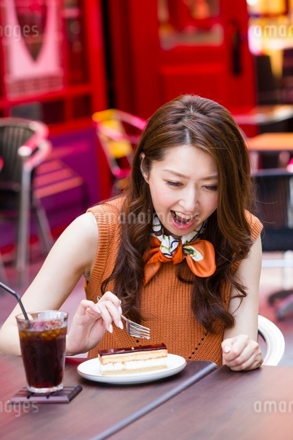 オープンカフェでケーキを食べる女性の写真素材 [FYI03054024]