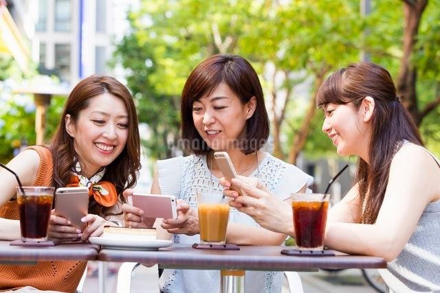オープンカフェでスマホを操作する女性の写真素材 [FYI03054025]