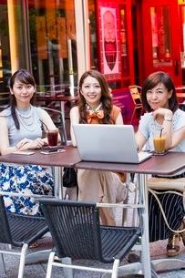 オープンカフェでパソコンを開く女性の写真素材 [FYI03054026]