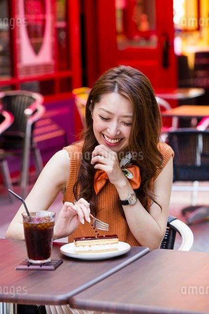 オープンカフェでケーキを食べる女性の写真素材 [FYI03054033]