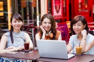 オープンカフェでパソコンを開く女性の写真素材 [FYI03054037]