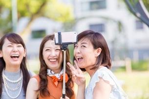 自撮り棒で写真を撮る女性の写真素材 [FYI03054094]
