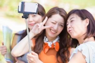 自撮り棒で写真を撮る女性の写真素材 [FYI03054097]