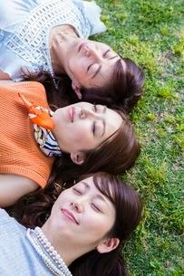 芝生に寝転ぶ女性の写真素材 [FYI03054101]