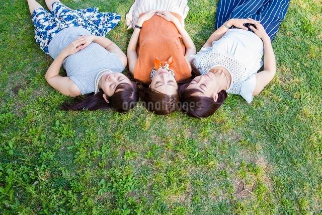 芝生に寝転ぶ女性の写真素材 [FYI03054103]