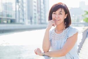 街中の川沿いに立つ女性の写真素材 [FYI03054104]