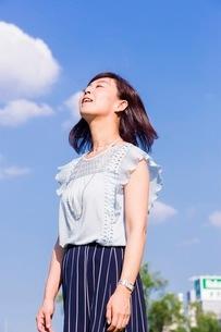 青空を背景に立つ女性の写真素材 [FYI03054109]
