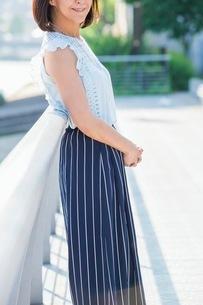 街中の川沿いに立つ女性の写真素材 [FYI03054113]