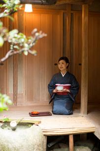 お茶を持つ着物姿の女性の写真素材 [FYI03054399]
