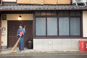 ほうきで掃く着物姿の女性の写真素材 [FYI03054407]