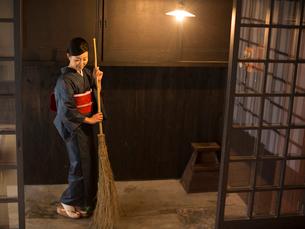 玄関掃除をする着物姿の女性の写真素材 [FYI03054411]