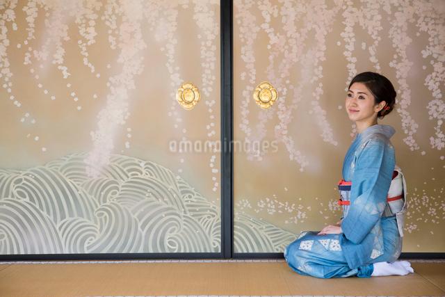 襖絵の前に正座する着物姿の女性の写真素材 [FYI03054474]
