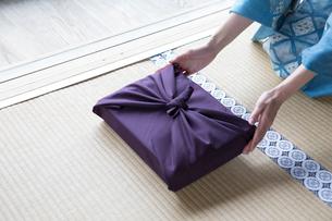 小包を差し出す着物姿の女性の写真素材 [FYI03054476]